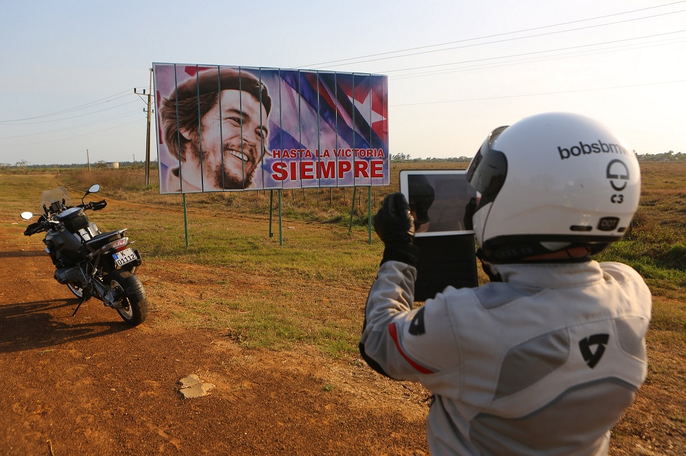 Bob Henig of Bob's BMW with Che Guevara billboard, Cuba; copyright Christopher P Baker