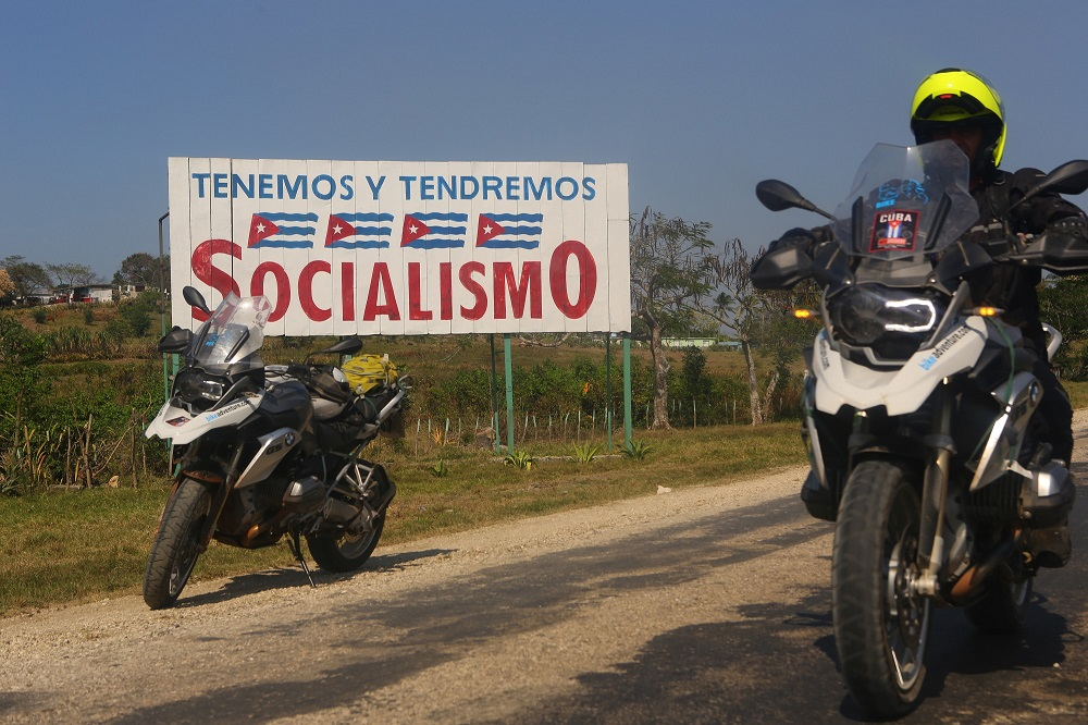 MotoDiscovery group member passing socialist billboard, Cuba; copyright Christopher P Baker